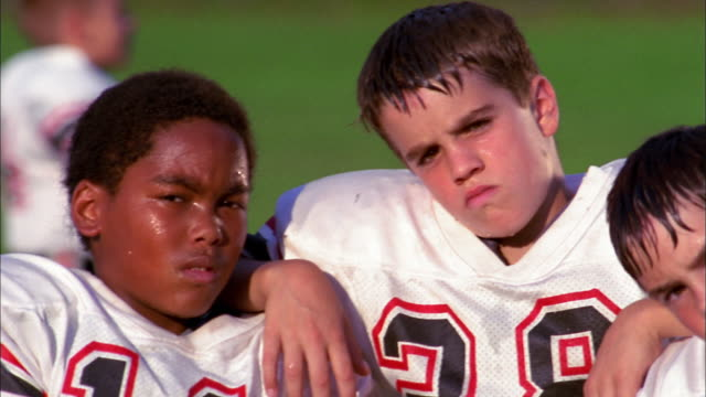 Close up pan three young boys in football uniforms looking seriously at CAM