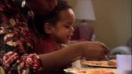 Close up pan toddler in mother's lap eating at dinner table / putting parmesan on food