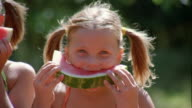 Close up pan two girls in pigtails eating slices of watermelon / New York