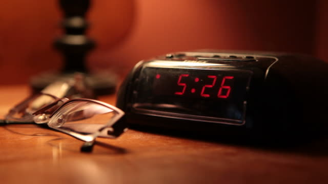 Close Up pan,left , A hand gropes for the snooze button on an alarm clock. /