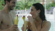 Close up panning shot of couple drinking tropical cocktails in swimming pool / Arenal, La Fortuna, Costa Rica