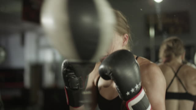 Close up panning shot of female boxer working out with speed ball / Lehi, Utah, United States