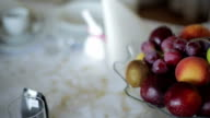 Close up panning shot of Fruits and cups on table
