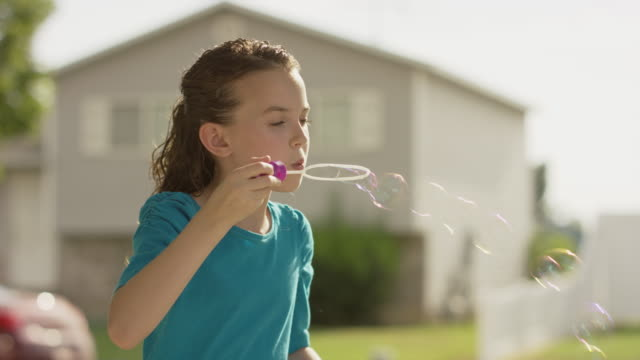 Close up panning shot of girl blowing bubbles outdoors / Provo, Utah, United States