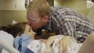 Close up panning shot of man kissing forehead of wife after childbirth / Midvale, Utah, United States