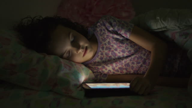Close up panning shot of mother removing digital tablet from bed of daughter / Provo, Utah, United States
