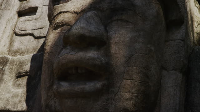 Close up panning shot of stone face at Mask Temple / Mask Temple, Lamani, Belize,