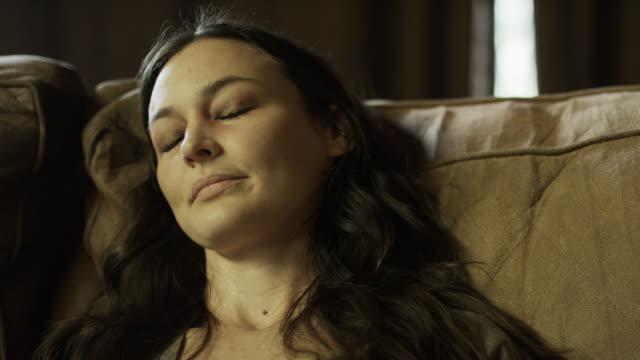 Close up panning shot of woozy intoxicated woman on sofa / Springville, Utah, United States