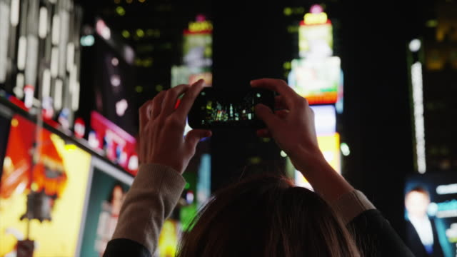 Close up panning shot of young woman using camera phone in Times Square at night / New York City, New York, United States