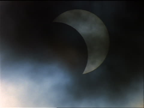 close up partial solar eclipse after totality with clouds moving in foreground / Summer 1999