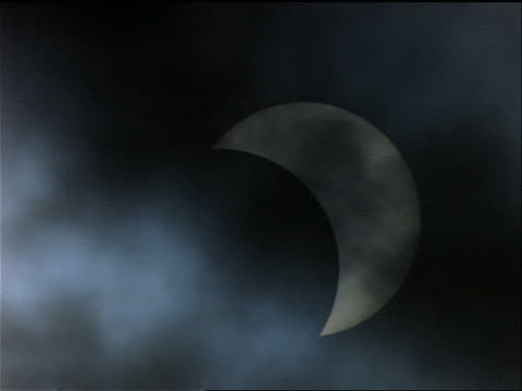 close up partial solar eclipse past totality with clouds moving in foreground