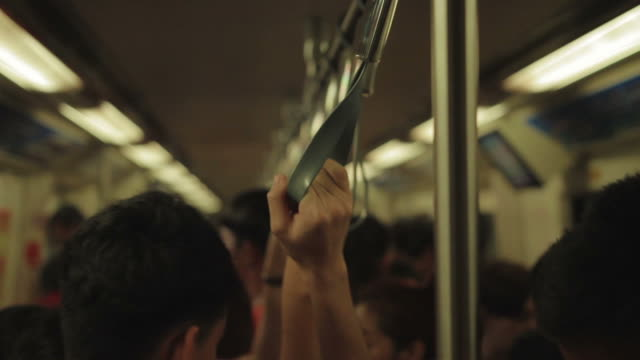 close up : people hands gripping handle bars in subway train
