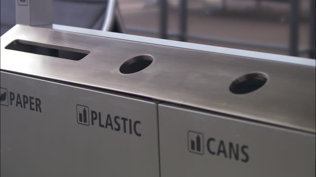 Close up person putting plastic bottles in recycling bin/ Seattle