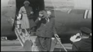 close up plane propellor spinning / Prime Minister Robert Menzies off plane tips hat followed by wife Pattie Menzies and Harold Holt and is greeted...