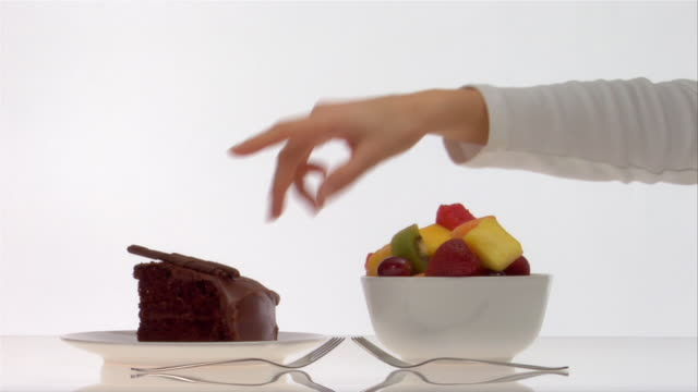 Close up plate of chocolate cake and bowl of fruit salad/ hand entering and picking up fruit salad