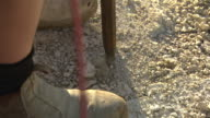 close up pneumatic jack hammer drilling into concrete hands and feet of operator seem in some shots
