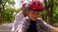 close up point of view boy wearing helmet riding bicycle with man running + cheering behind