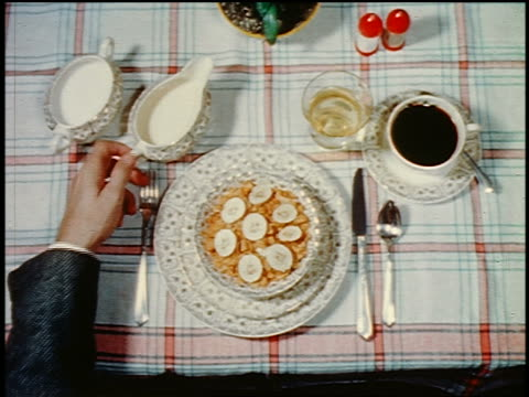 1959 OVERHEAD close up point of view man's hand pouring milk from pitcher onto bowl of cereal near coffee cup