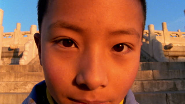 close up PORTRAIT Asian boy's face with Temple of Heaven in background / Forbidden City, Beijing, China