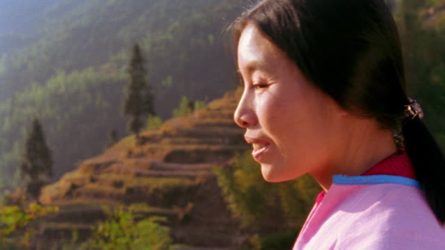 close up PORTRAIT Bai woman turning + smiling with terraced farmland in background / Dali, China