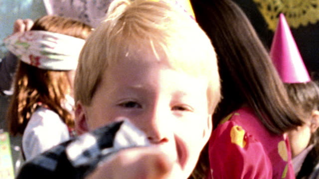 OVEREXPOSED close up PORTRAIT blonde boy smiling + pointing at camera at party / other children in background