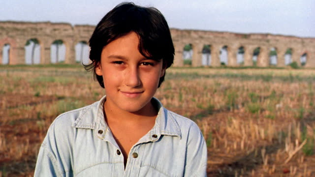 close up PORTRAIT boy standing in field looking serious then smiling / aqueduct in background / Italy
