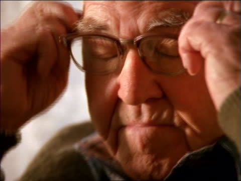 close up PORTRAIT face of senior man putting on eyeglasses + smiling