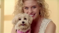 Close up portrait girl holding Maltese-Toy Poodle mix dressed in outfit
