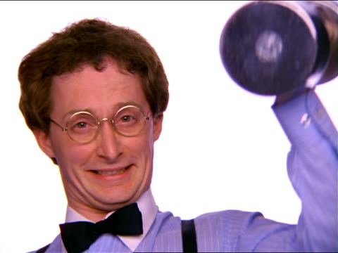 close up PORTRAIT nerdy man in eyeglasses looking at camera + struggling to lift dumbbell / falls over
