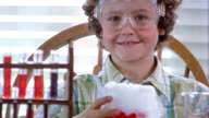 Close up portrait of elementary school student with beaker giving off dry ice in chemistry class