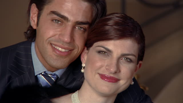 Close up portrait of young couple in formal wear embracing and smiling at CAM