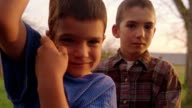 close up PORTRAIT point of view toward two boys / one smiling + holding rope of tree swing / Montana
