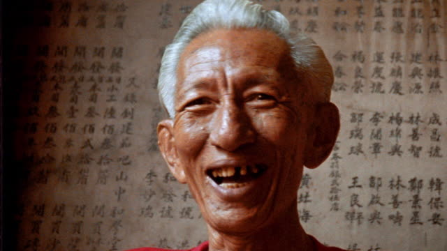 close up PORTRAIT senior Asian man smiling + laughing in front of Asian script / Java, Indonesia