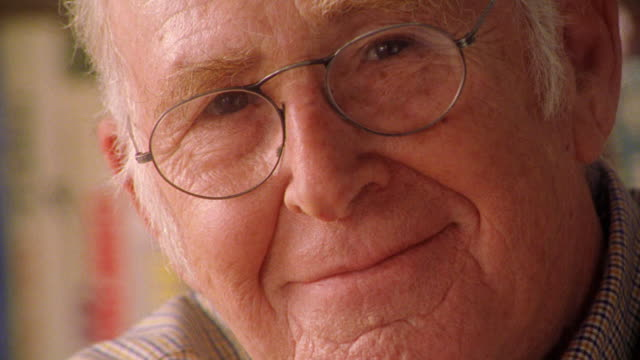 close up PORTRAIT senior man in eyeglasses smiling indoors