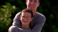 CANTED close up PORTRAIT taller teen boy hugging smaller boy outdoors / both smiling