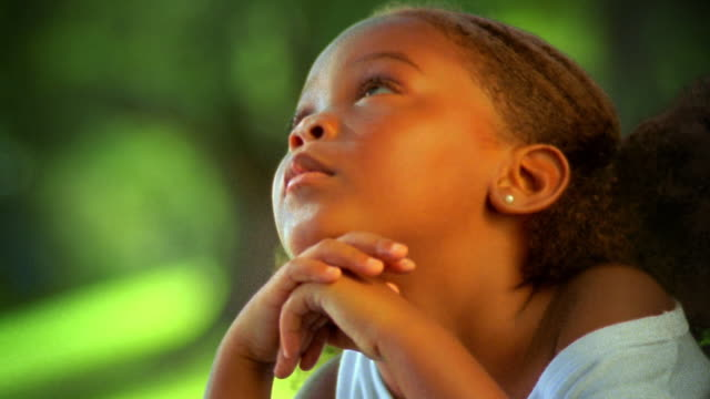 close up PORTRAIT young Black girl looking up + resting chin on hands outdoors / Florida