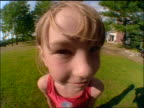 FISHEYE close up PORTRAIT young blonde girl smiling at camera outdoors