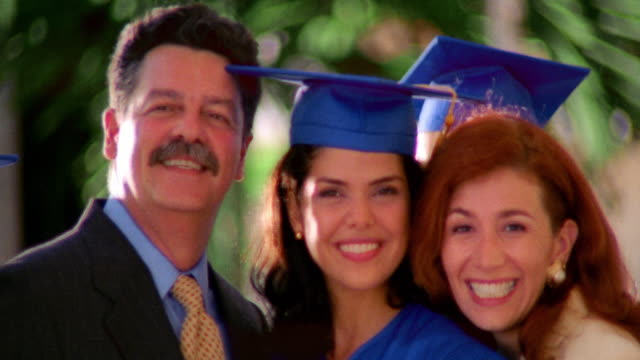 close up PORTRAIT young Hispanic woman wearing cap + gown hugging parents / Florida
