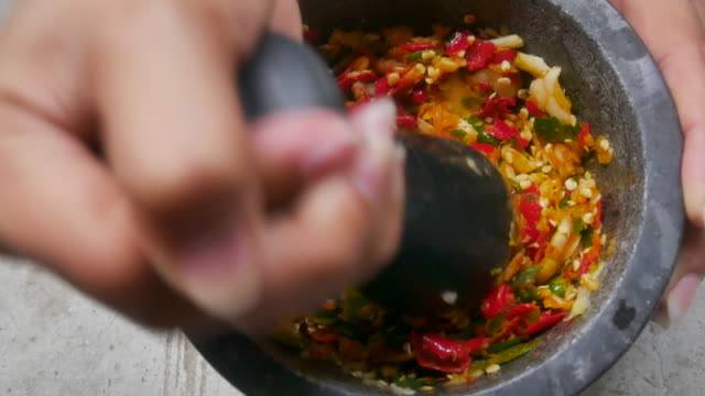 Close up pounding fresh herbs in a mortar with a pestle