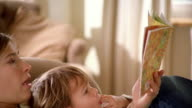 Close up pregnant woman reclining in chair and reading to young girl while feeling her stomach