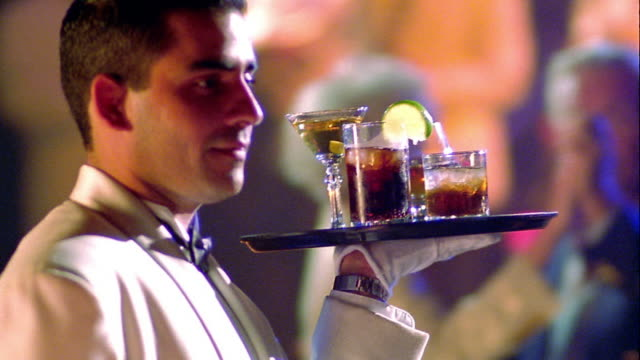 close up PAN PROFILE waiter walking past couples dancing with tray of cocktails in nightclub