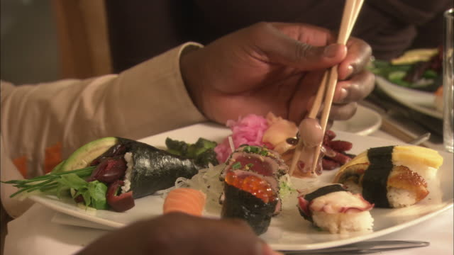 Close Up push-in tracking-left - A hand holds a tiny octopus with a pair of chopsticks over a plate of sushi