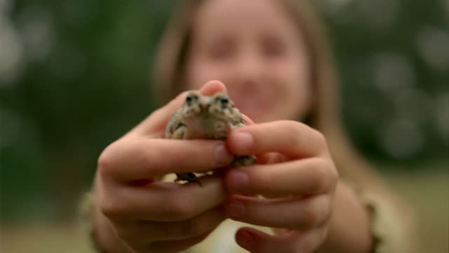 Close up rack focus portrait of girl holding frog and smiling at CAM