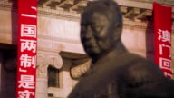 close up rack focus statue of Mao Zedong with Chinese writing on banner on building in background / The Bund, Shanghai