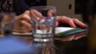 close up rack focus PAN woman's + man's hands tapping pen, writing + picking up glass of water / conference table
