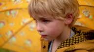 Close up rack focus young blonde girl in raincoat with umbrella walks through trees away from camera / Nova Scotia