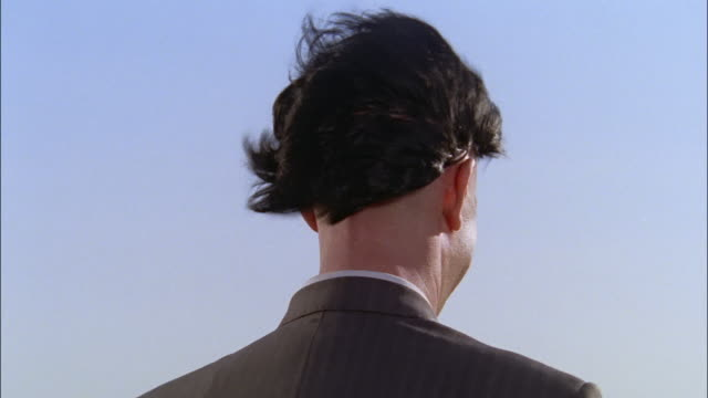 Close up rear view of man wearing hat / wind blowing hat off / wig blowing off and man feeling bald head