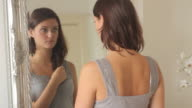 Close up rear view of woman looking at her reflection in mirror
