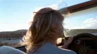 Close up rear view woman driving convertible in desert / Baja, Mexico
