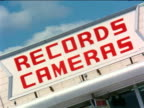 1963 CANTED close up 'Records Cameras' sign on store / industrial